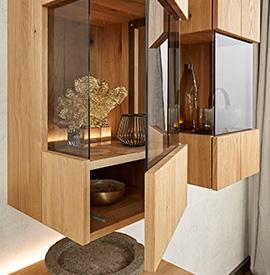 Zwei hängende, hölzerne Vitrinen mit Dekoration und einer offenen Glastür