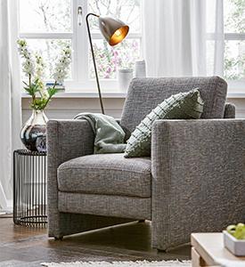 Hellgrauer Sessel mit grünem Kissen und moderner Stehleuchte