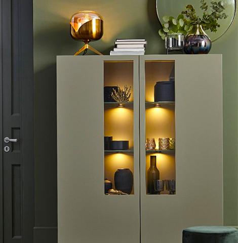 Grüne Vitrine mit beleuchteten Einlegeböden und Glaseinsätzen in den lackierten Türen