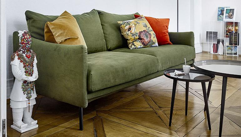Grünes Sofa mit bunten Deko-Kissen und zwei runden Beistelltischen