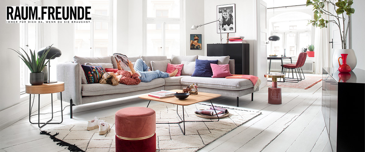 Weißes Sofa der Marke RAUM.FREUNDE mit liegender blonden Frau in einem hellen Wohnzimmer