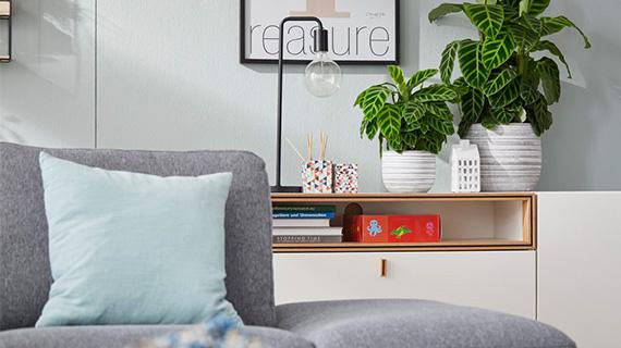 Grauer Hocker vor einem weißen Sideboard mit Pflanzen und einer Lampe