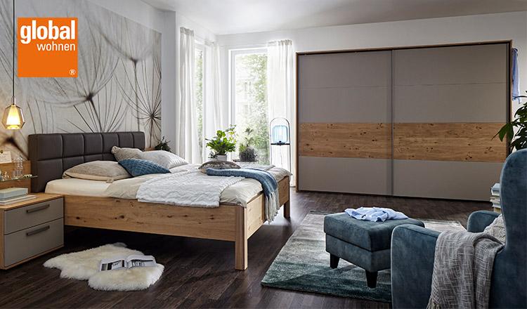 Modern eingerichtetes Schlafzimmer mit dem global wohnen Logo in der linken oberen Ecke