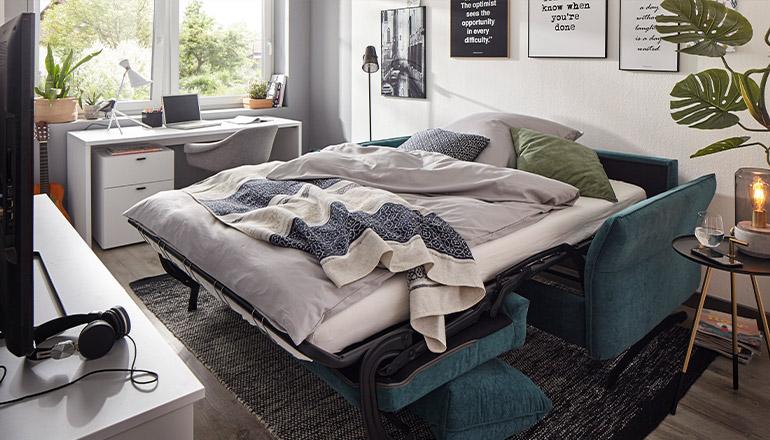 Blaues 2-Sitzer Sofa mit Schlaffunktion umgebaut zu einem bequemen Bett