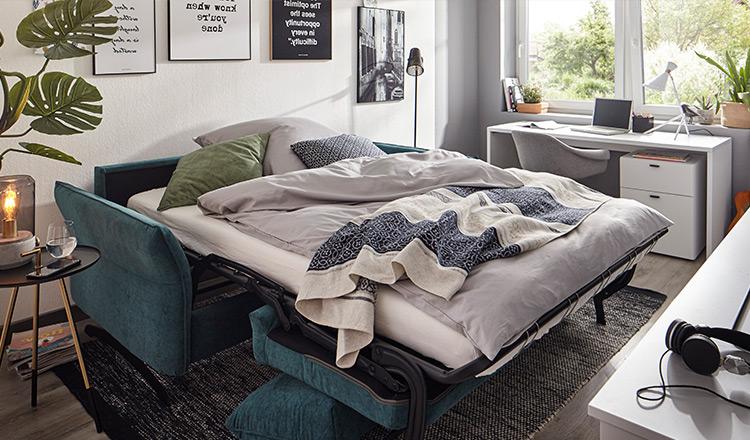 Blaues Sofa umgebaut in ein bequemes Bett mit grauer Bettwäsche