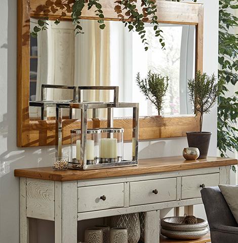 Silberne Deko auf einem schmalen Beistelltisch vor einem Spiegel mit Holzrahmen