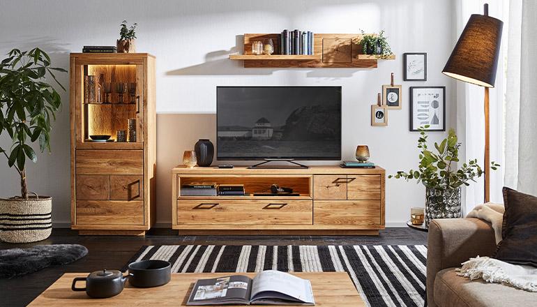Wohnprogramm aus massiver Eiche mit Vitrine und Lowboard auf dem ein Flatscreen TV steht