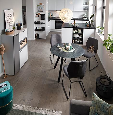 Essküche mit einem runden Esstisch und drei grauen Esszimmerstühlen