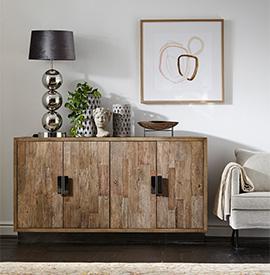 Kommode aus naturbelassenem Massivholz mit schwarzen Griffen neben Sofa