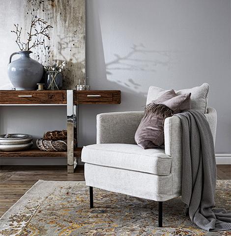 Weiß-grauer Sessel mit Wohndecke und Kissen vor Konsolentisch aus Massivholz