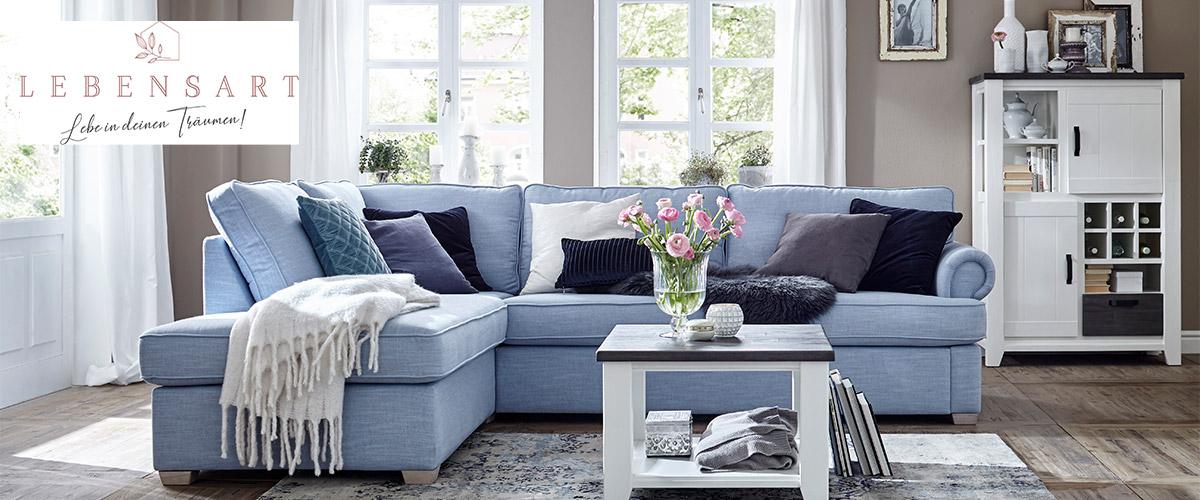 Hellbaues Sofa neben weißer Anrichte und Couchtisch aus Massivholz