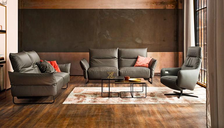 Grau-grüne Ledergarnitur mit zwei 2-Sitzern und einen Relaxsessel um ein edles Couchtisch-Set im Wohnzimmer
