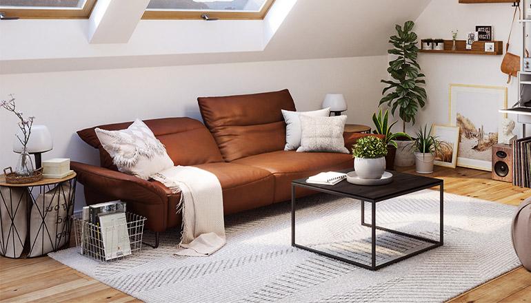 Cognacfarbenes Sofa mit weißen Kissen und Decken vor einem schwarzen Couchtisch