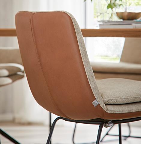 Rückenansicht eines Esszimmerstuhls mit Kombibezug aus Stoff in Beige und Leder in Braun