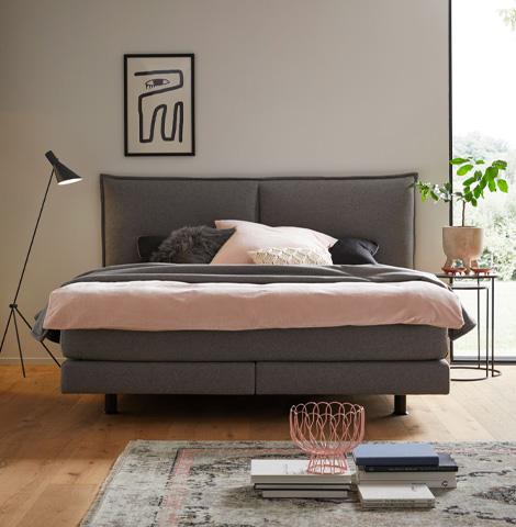 Graues Bett von contur mit hellrosafarbener Bettwäsche im modernen Schlafzimmer