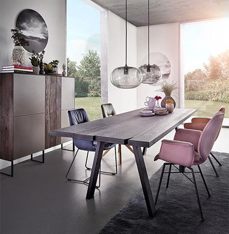 Elegantes Esszimmer mit dunklem Holztisch und rosa sowie grauen Polsterstühlen bei Sonnenuntergang