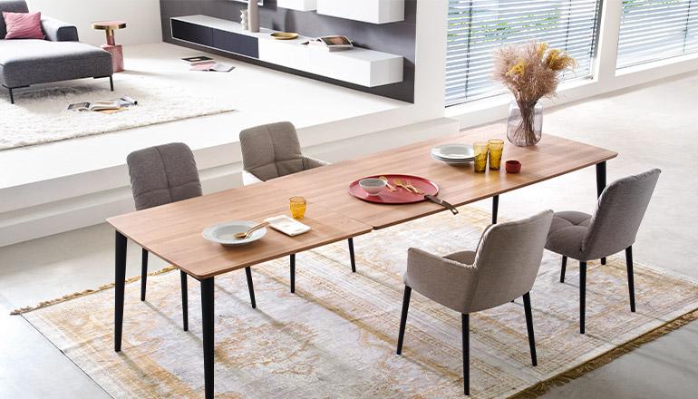 Holz- Esstisch mit grauen Stühlen und rosa Deko