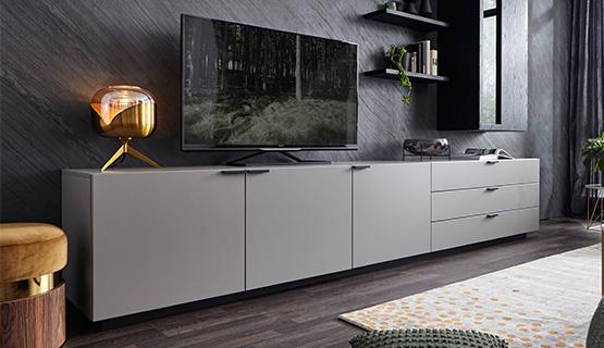 Hellgraues Lowboard mit schlankem TV vor einer dunklen Schieferwand neben goldenem Hocker