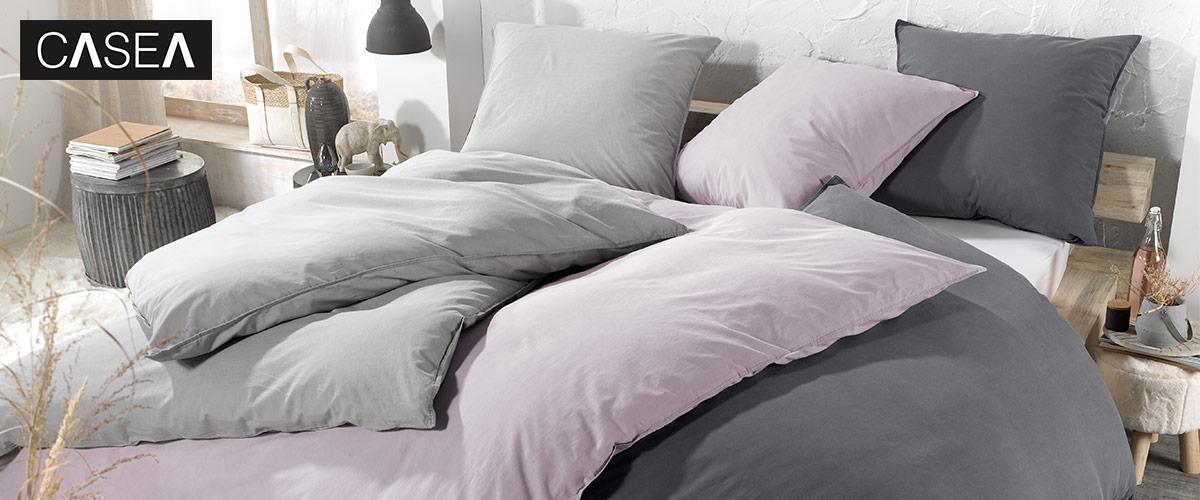 Rosa, graue und dunkelgraue Bettwäsche auf bequemen Bett im Schlafzimmer