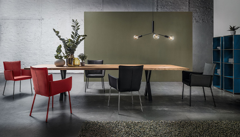 Esszimmer mit großem Esstisch und roten sowie schwarzen Stühlen