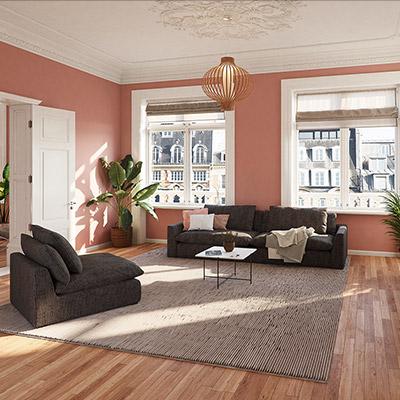 Sofa-Garnitur aus Sofa und Sessel im dunklen Petrol Farbton in einem Altbau-Wohnzimmer mit rosafarbener Wand