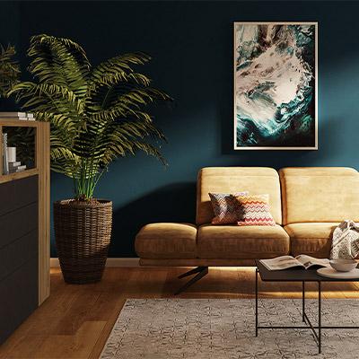 Filigranes, gelbes Sofa mit verstellbaren Armlehnen vor einer türkisfarbenen Wand