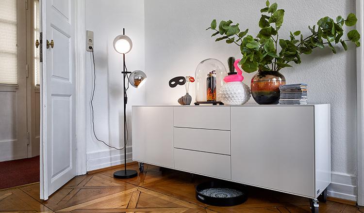 Weißes Lowboard mit verschiedenen Dekoartikeln neben einer modernen Lampe