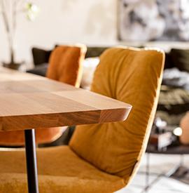 Stühle in Gelb und Orange um einen braunn Holztisch