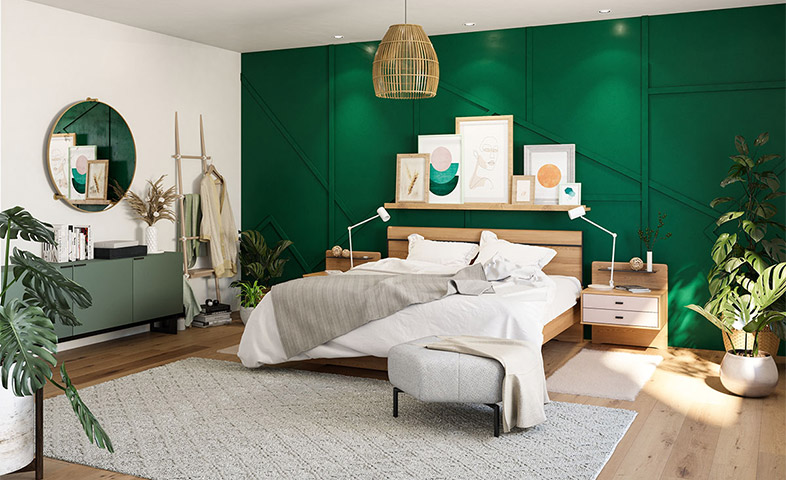 Bettgestell aus massivem Holz neben einem mintgrünem Sideboard und vor einer dunkelgrünen Wand