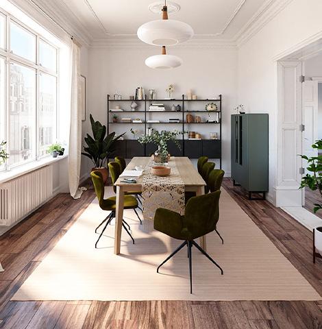 Schlammgrüne Esszimmerstühle um einen massiven Holztisch vor schwarzem Wandregal und mintgrünem Highboard