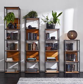 Mehrere Holz-Regale, die mit Deko, Büchern und Pflanzen geschmückt sind