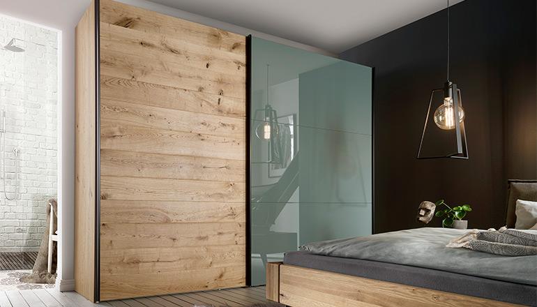 Schrank mit Schwebetür aus Holz und grüngrauen Glas vor einem Massivholzbett