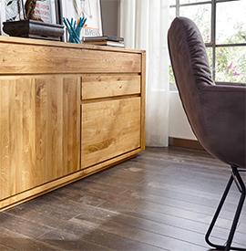 Detailbild einer Kommode aus hellem Massivholz, die auf einem dunkelbraunen Holzboden steht
