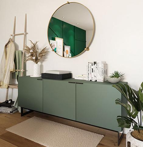 Mintgrünes Sideboard auf dunklem Holzboden vor weißer Wand mit einem runden Spiegel mit Goldrahme