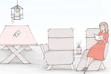 Frau stöbert durch ein Heft auf einem Sessel