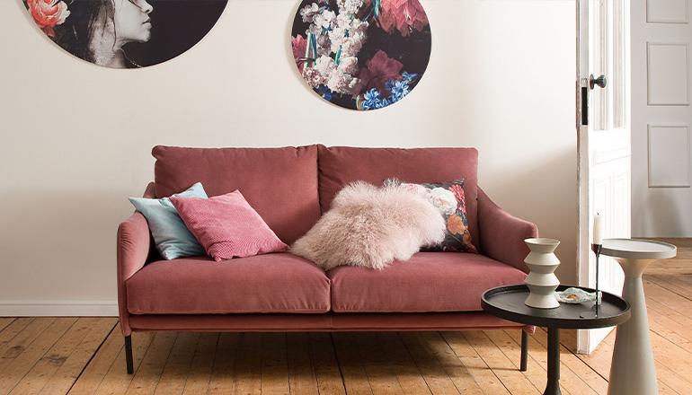 Hellrotes Sofa mit rosa- und hellblauem Kissen im Pastellton