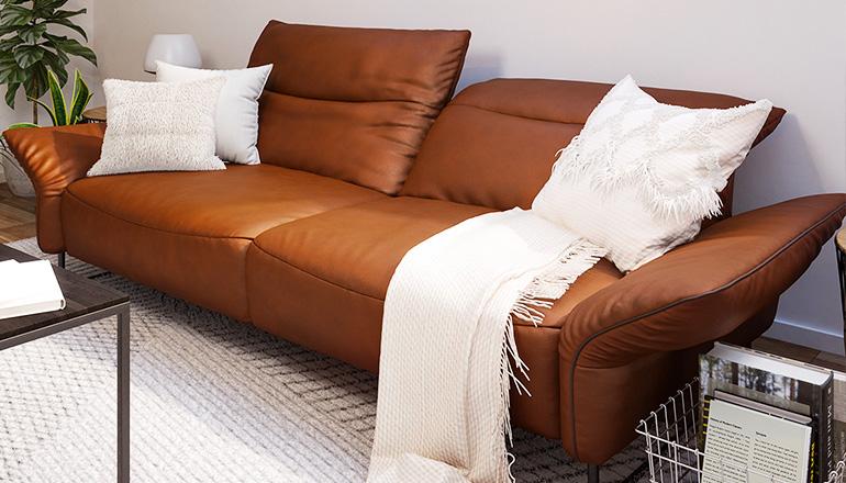 Hellbraunes Dreisitzer-Sofa im Cognac-Ton aus echtem Leder mit weißen Kissen und Decken