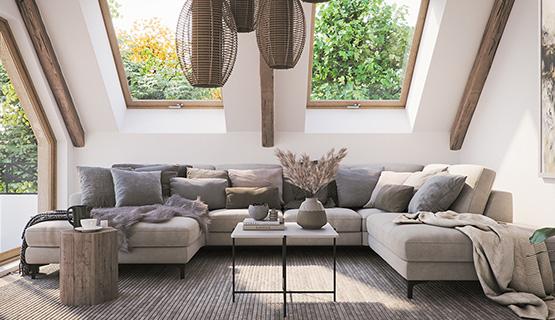 Weiße, große Wohnlandschaft mit vielen Kissen in einem Wohnzimmer mit Dachschrägen