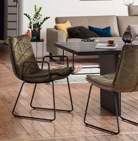 Dunkelgrüner Armlehnstuhl mit schwarzen Kufen passend zum schwarzen Esstisch