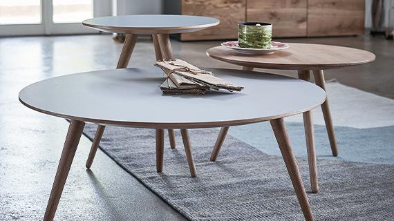 Drei unterschiedlich hohe Beistelltische mit runden Tischplatten und schrägen Füßen