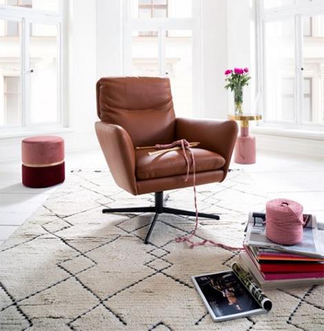 Cognacfarbener Drehsessel kombiniert mit rosa Hocker im Glamour-Stil
