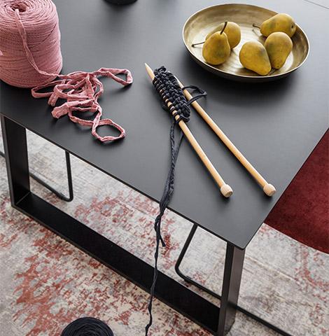 Schwarzer Esstisch mit Stricknadeln und einer Schale mit Birnen