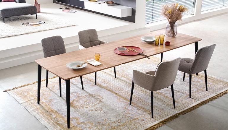 Esstisch mit Tischplatte aus Massivholz neben gepolsterten Stühlen der Marke RAUM.FREUNDE