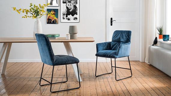 Zwei dunkelblaue Stühle vor einem Massivholz-Esstisch mit weißen Füßen