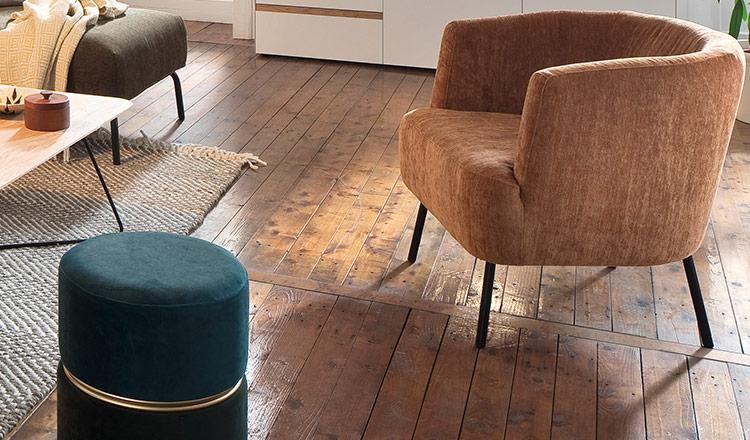 Brauner Loungesessel neben einem grünen Hocker auf einem alten Holzboden
