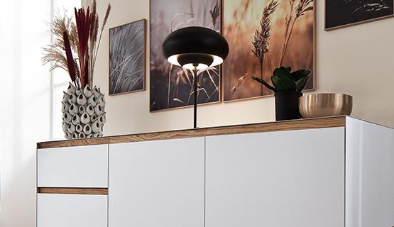 Weiße Kommode mit Massivholzgriffen dekoriert mit Pflanzen, Bildern und einer Lampe