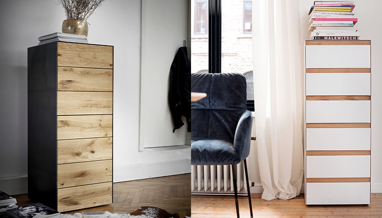 Eine schwarze Kommode mit Holzfronten und eine weiße Kommode mit Griffleisten aus Holz