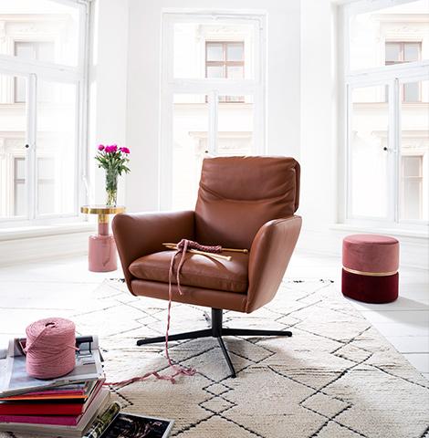 Loungesessel aus braunem Leder neben einem Hocker und einem Beistelltisch