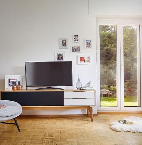 Lowboard aus Holz mit zwei weißen Schubladen und einem schwarzen Element mit Akustikstoff