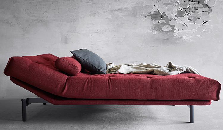 Rotes, umgebautes Schlafsofa mit zwei Kissen und einer beigen Wohndecke